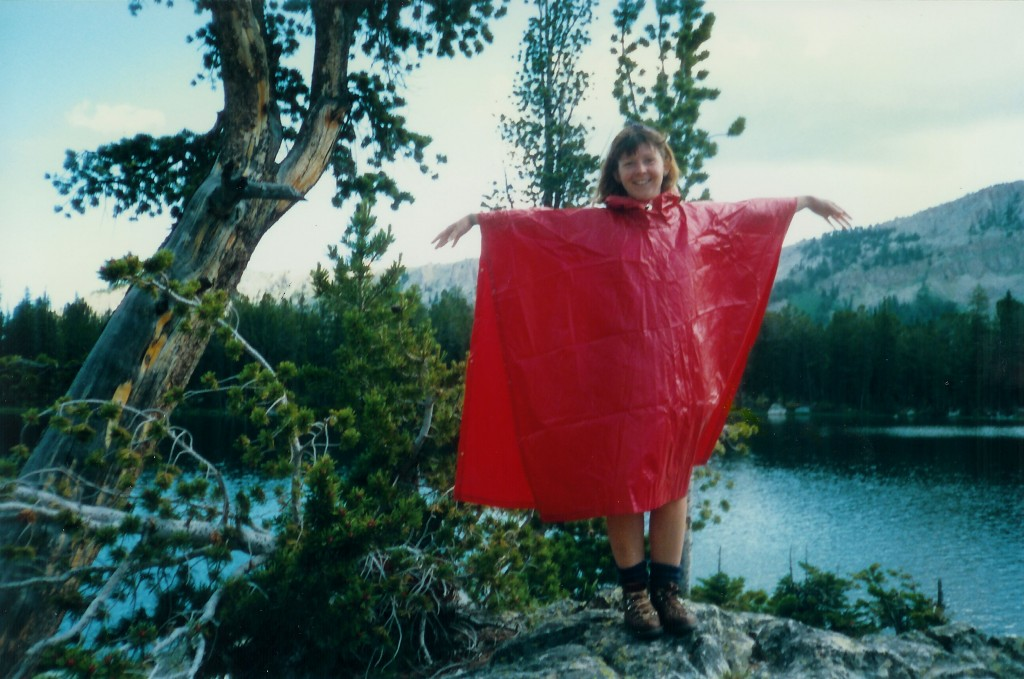 Photo of DJ Choupin in a red cape by a high mountain lake in 1980s Jackson Hole