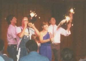 Photo of Ed Bachtel performs the national anthem as Stephan Alexander Parker, Holly Danner, and Dave Rohrer hold roadkills on a stick with sparklers to a standing ovation at the sold-out final 1988 performance of Roadkill Live!!!