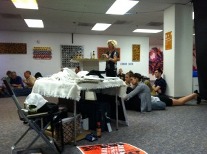 Photo of sprawling room only at the workshop concert performance of A Roadkill Opera on June 9, 2012. Production assistant Nina Ganz can be seen at the center of the spillover crowd, behind the table of swag.