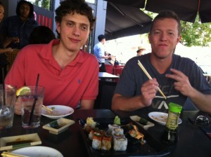 Photo of videographer Ben Ganz (at right) and assistant Jason Ganz eating sushi.