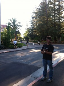 Photo of George Jahad on the campus of Stanford University in July 2013 holding a copy of If you see roadkill, think opera