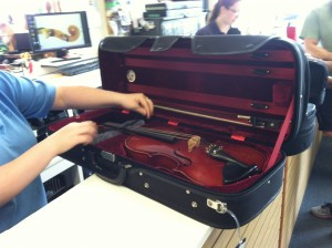 Alicia placing the mystery viola in a house case while it is held for evaluation at Lashof Violins.