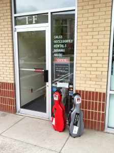 Photo of the red and the gray: twin cello-shaped viola cases set on the sidewalk in front of Lashof Violins in Gaithersburg, Maryland.