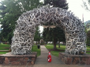 Photo of the a red, cello-shaped, fiberglass viola case under the elk antler arches in the town square in Jackson, Wyoming.