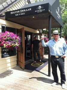 Photo of Stephan Alexander Parker holding up 3 fingers in front of the awning over the doorway to the Silver Dollar Bar.