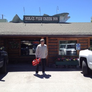 Photo of Author Stephan Alexander Parker in front of Nora's Fish Creek Inn, carrying his signature red, cello-shaped, fiberglass viola case.