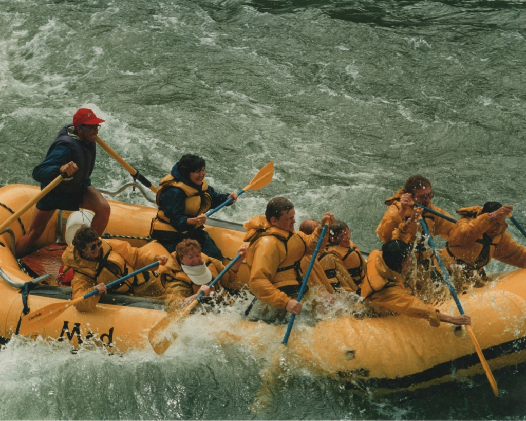 Photo of Stephan Alexander Parker guiding a yellow raft with 7 paddlers and two additional passengers through whitewater on the Snake River.