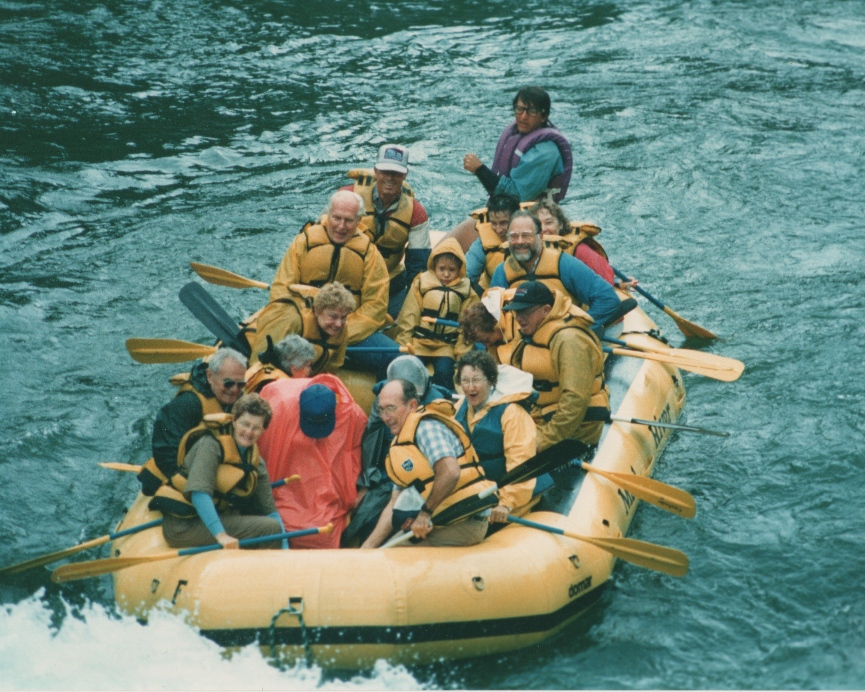 Photo of Parker guiding a raft full of paddlers