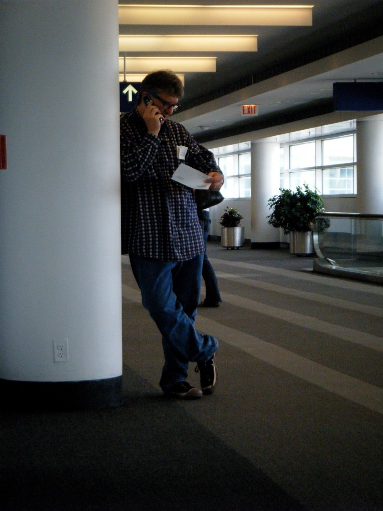 Photo of Parker on the phone leaning against a column at an international airport