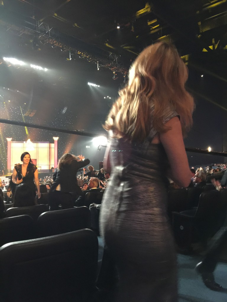 Photo of Jane Seymour in foreground as Weird Al Yankovich runs down the aisle to the stage in the background