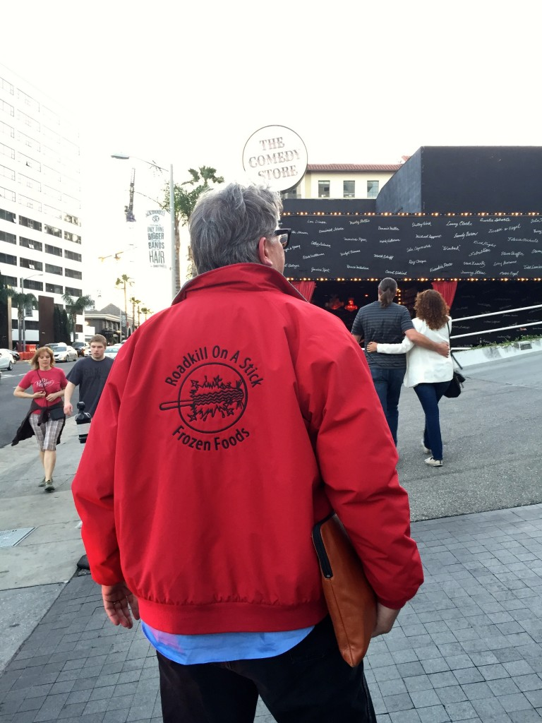 Photo showing Parker's back; he is wearing a red jacket with the Roadkill On A Stick Frozen Foods logo on the back