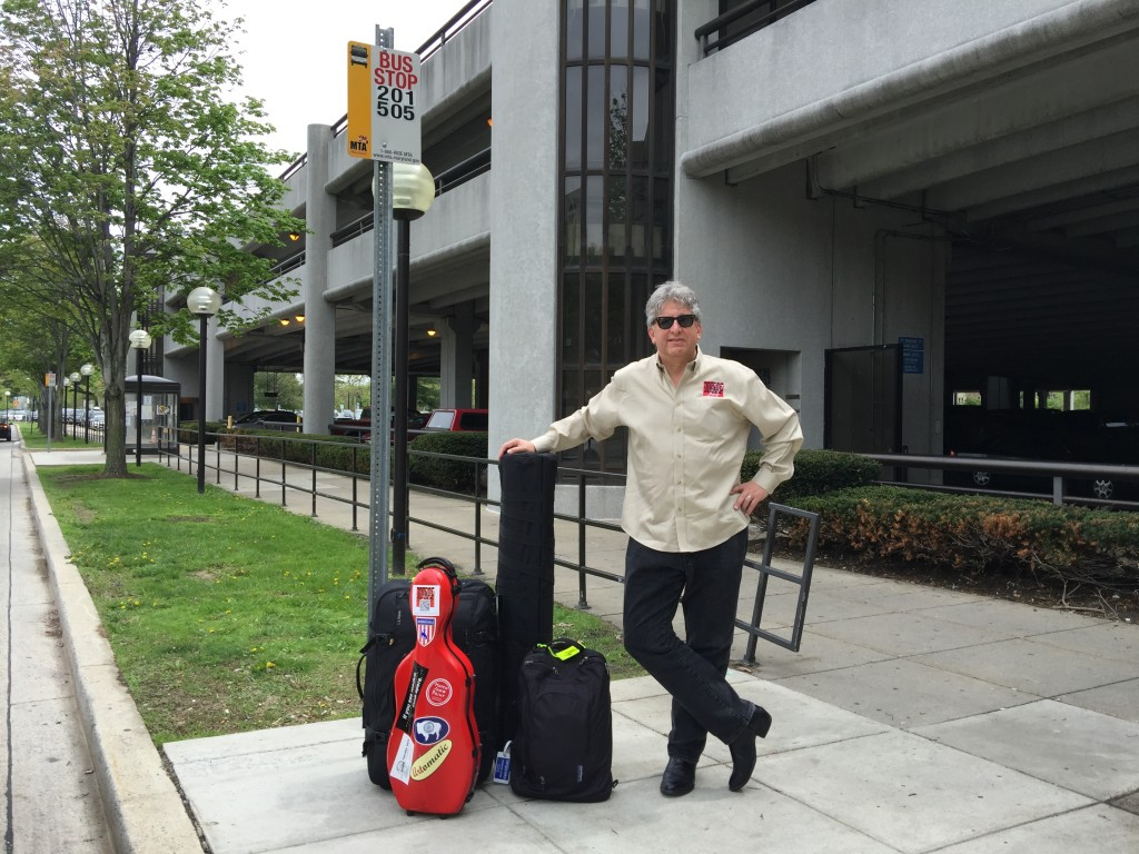 Photo of Parker with luggage at a bus stop