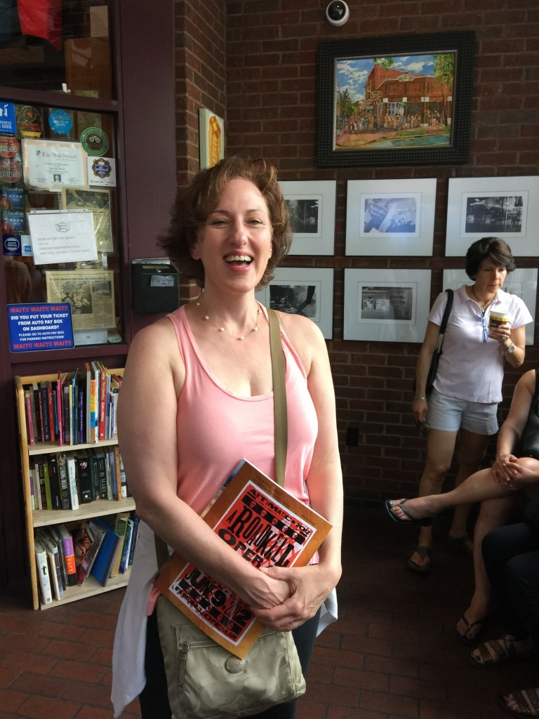 Photo of Stefani Novik standing in line at Pancake Pantry, holding a copy of the piano/vocal score for A Roadkill Opera