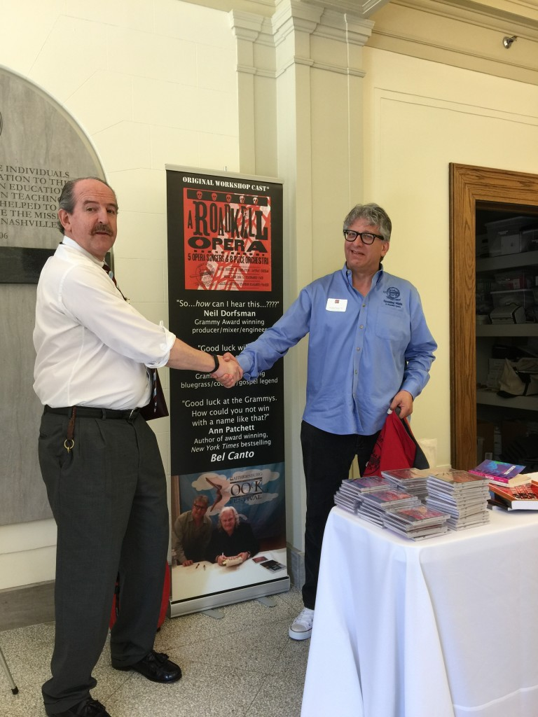 Photo of Durnan and Parker shaking hands in front of Durnan's office and Parker's pop-up banner