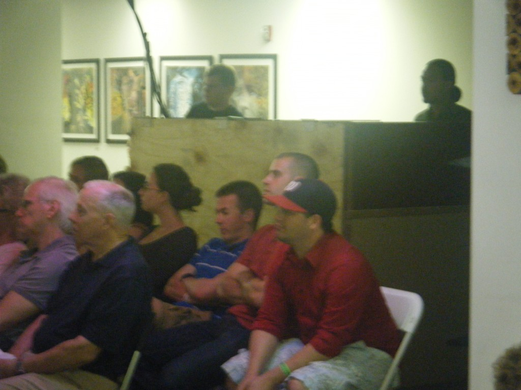 Photo of crowd sitting in front of audio booth
