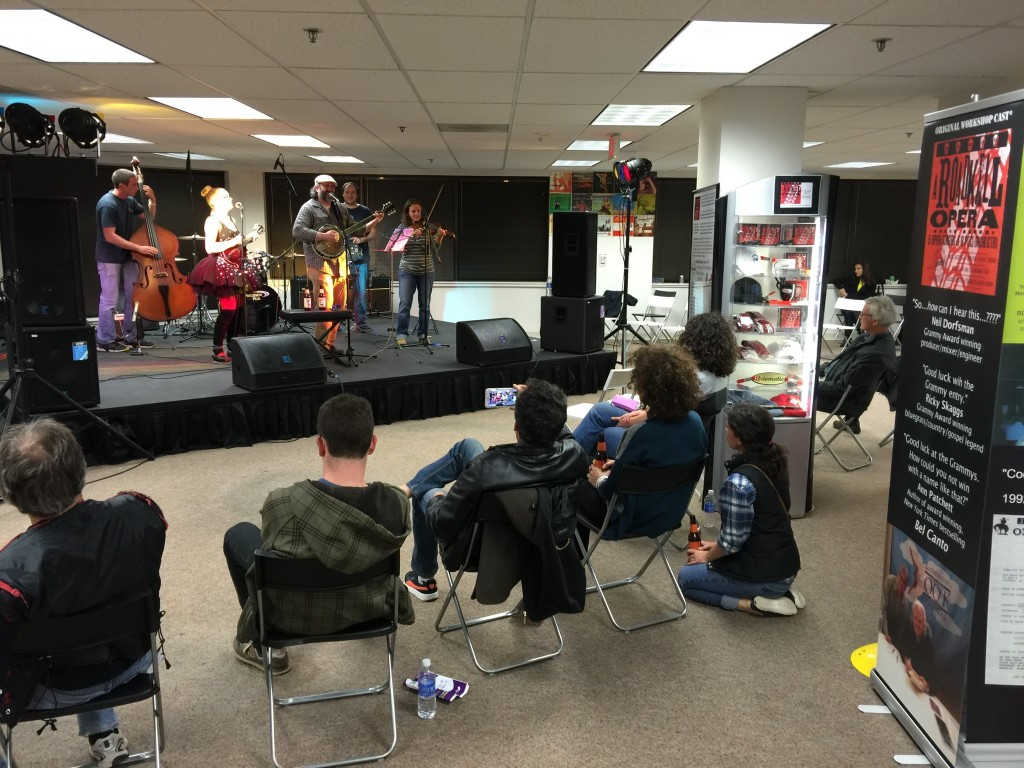 Photo of audience sitting by Parker's exhibit and watching a bluegrass band perform at Artomatic 2015