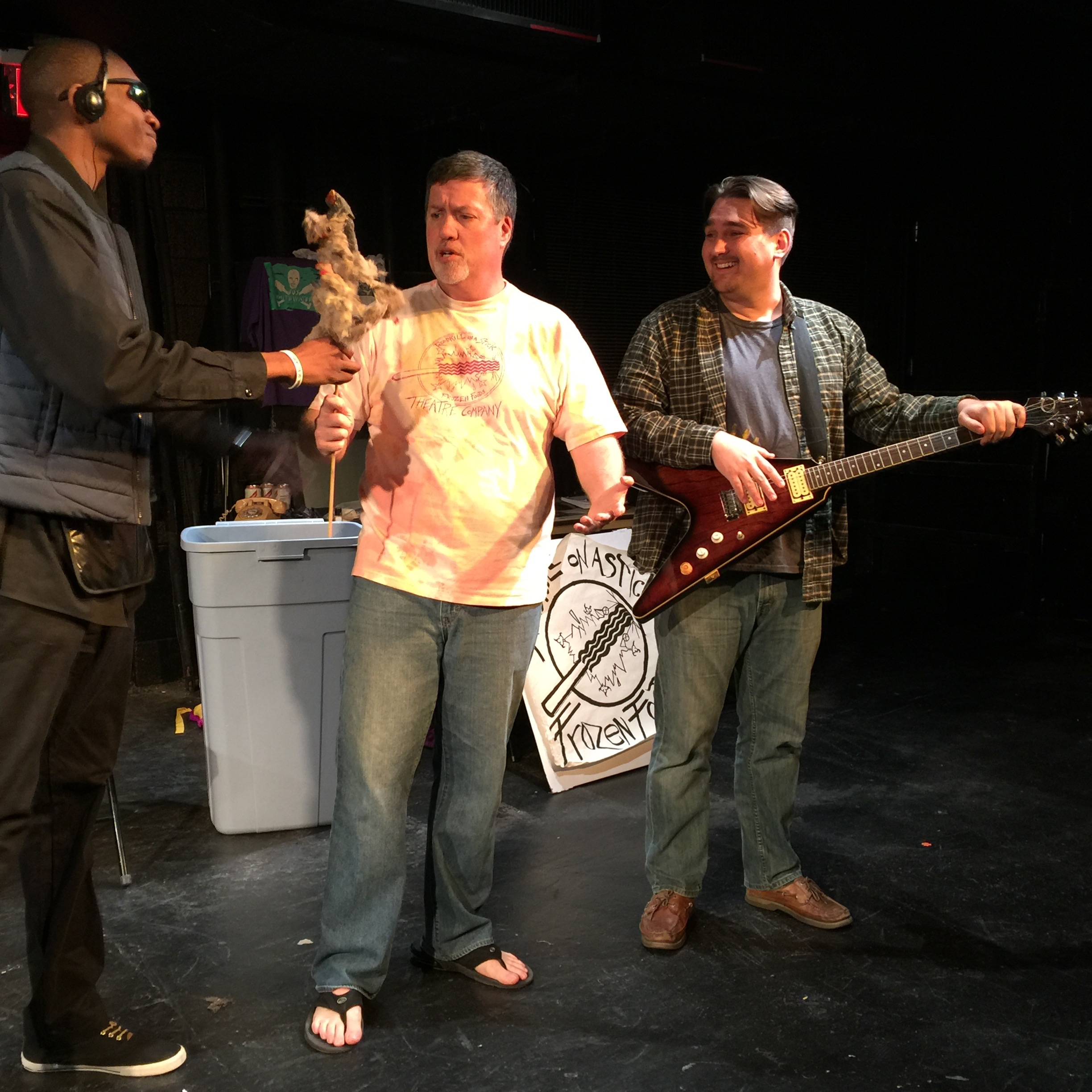 Photo of Marvin handing a roadkill on a stick to Stephan as Dave looks on