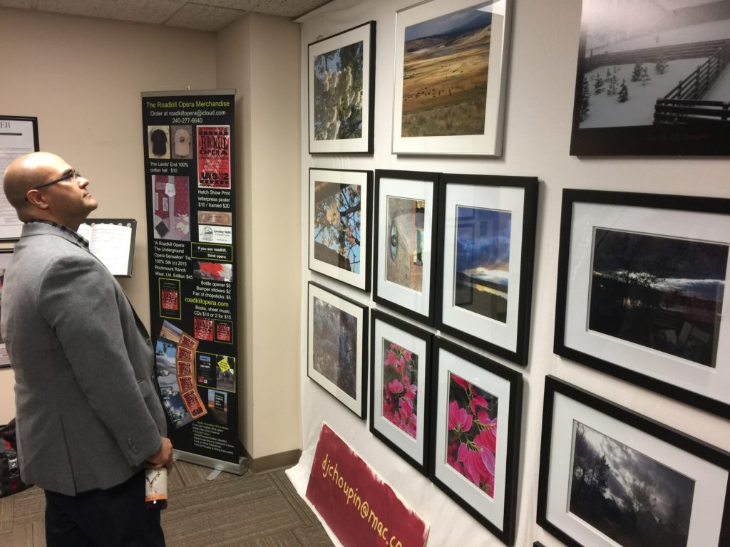 Photo of a man looking at DJ Choupin's photos at Artomatic 2017 in Crystal City, Virginia