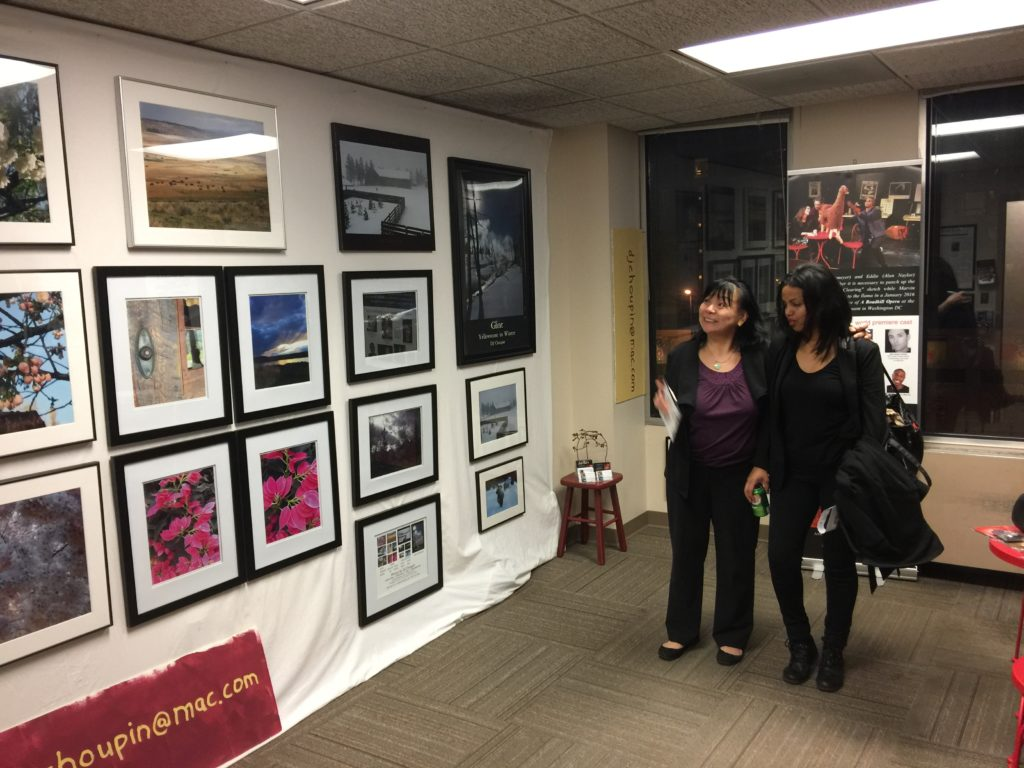 Photo of 2 women admiring CJ Choupin's photographs