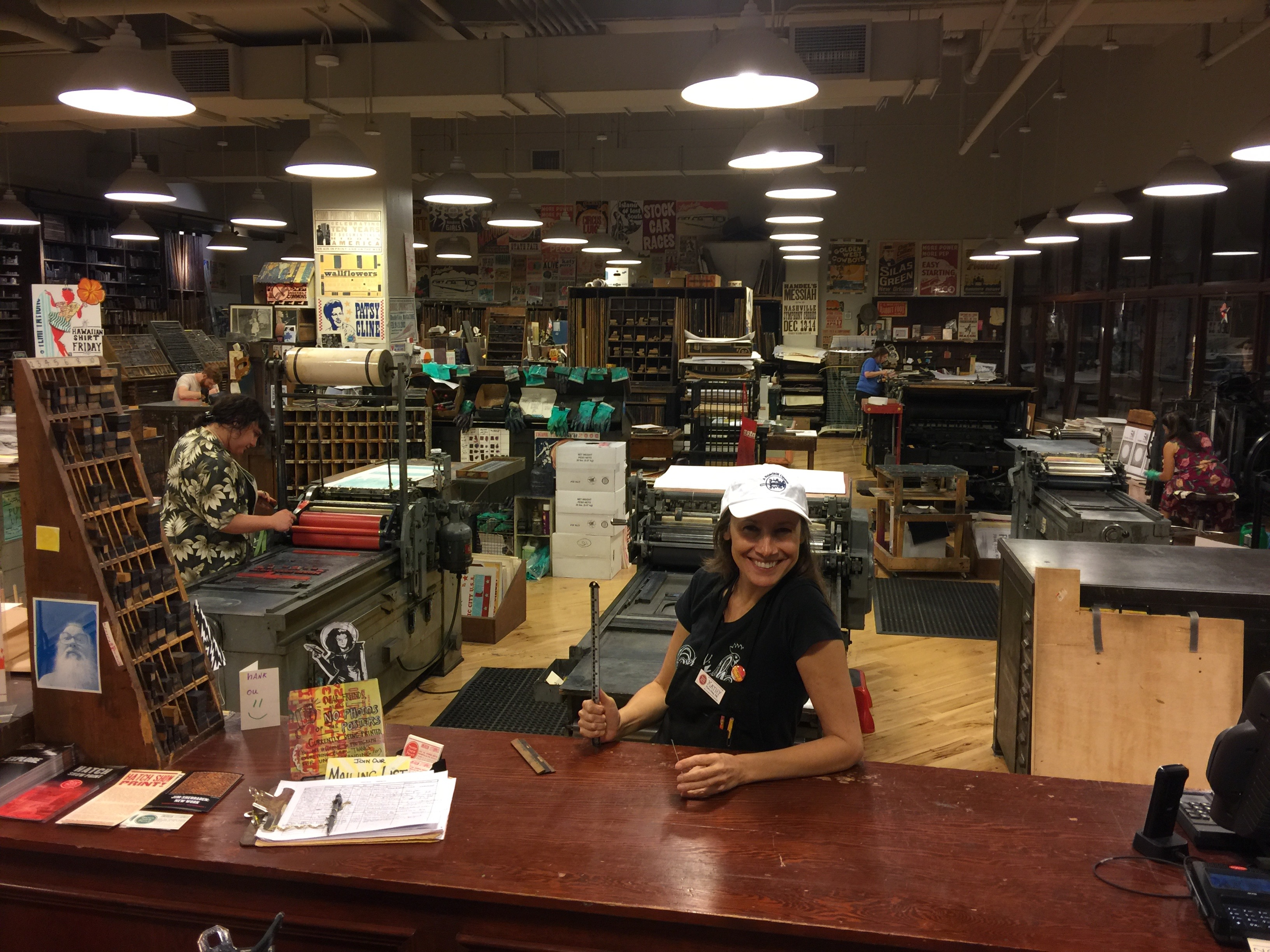 Photo of Kathy standing at service desk in front of the Hatch Show Print workshop full of presses