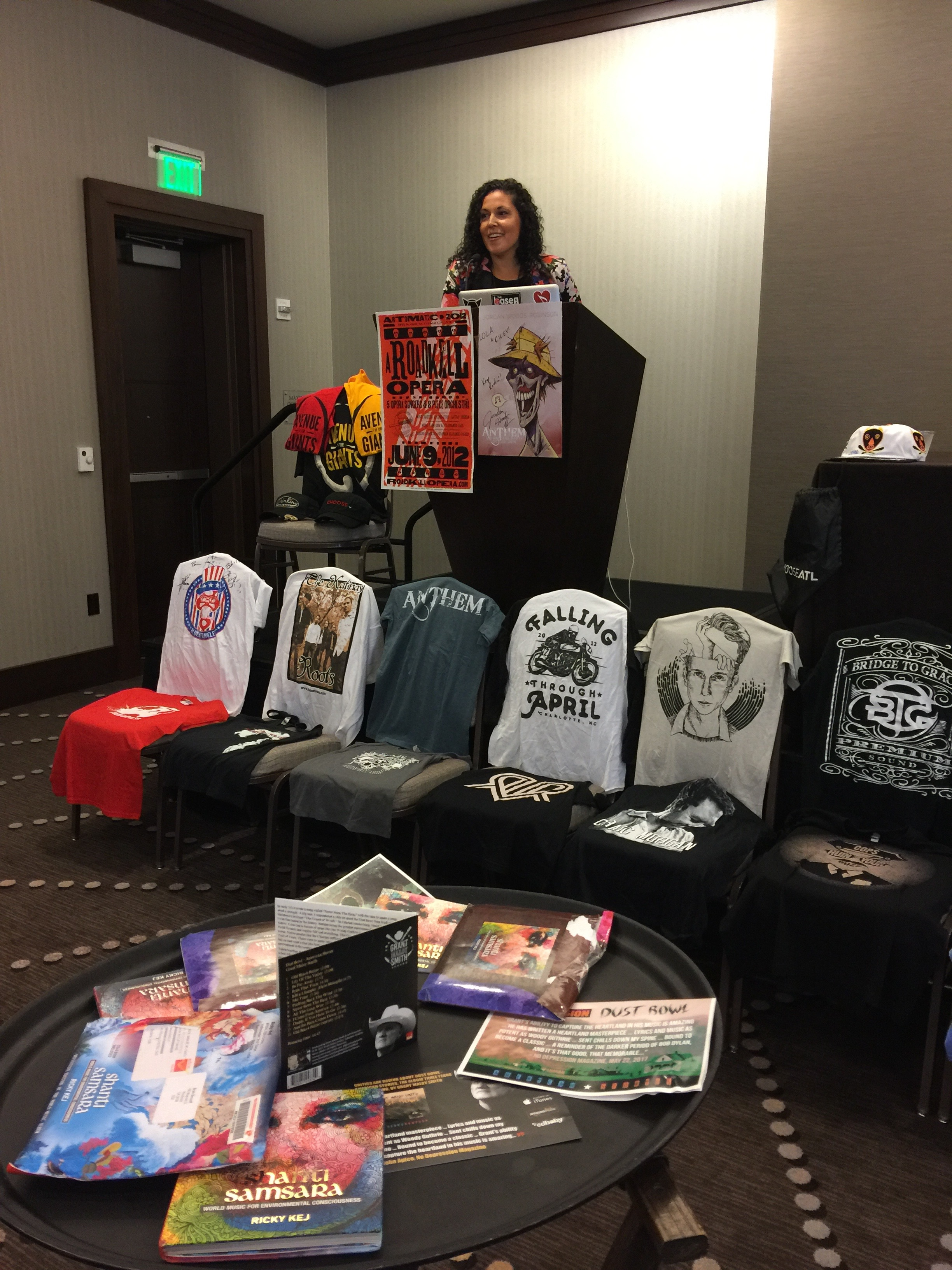 Photo of Vanessa Ferrer at the podium festooned with posters from a Walking Dead star and A Roadkill Opera. In front of the podium is a row of chairs with t-shirts and table vocoder with alternative swag, such as custom incense packaging from a reggae artist.