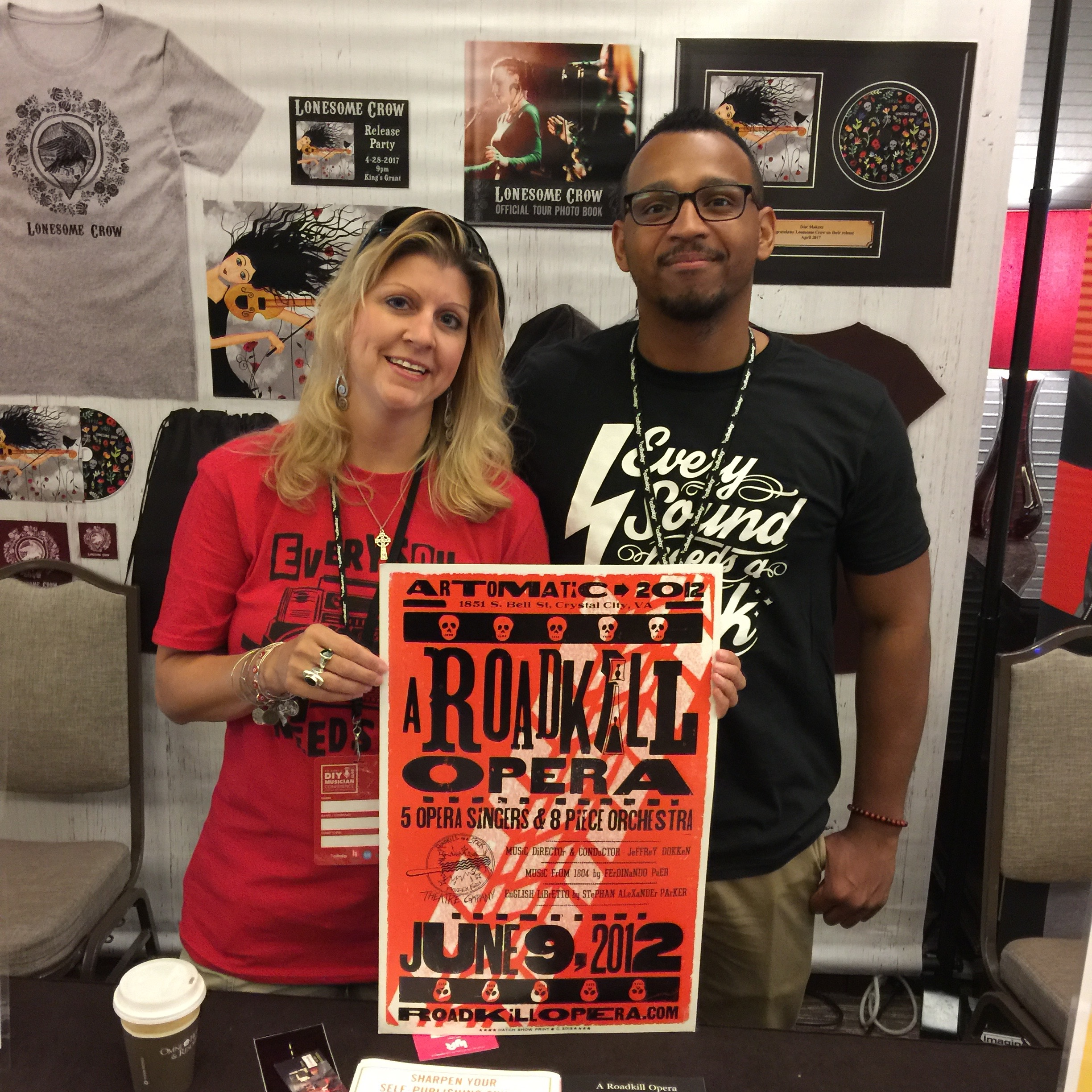 Photo of Michelle Borek and Josh Larkins of Disc Makers (AVL Digital Group) with A Roadkill Opera poster at the CD Baby DIY Musicians Conference 2017